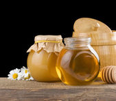 Honey and flowers isolted on black — Stock Photo