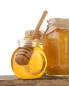 Jar of honey and stick on white — Stock Photo