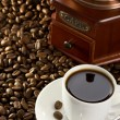 Cup of coffee and grinder — Stock Photo