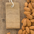 Nuts almond and tag price on wood — Stock Photo