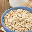 Bowl of oat and milk on wood — Stock Photo