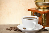 Cup of coffee with beans and grinder — Stock Photo