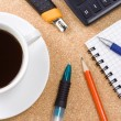 Checked notebook and cup coffee in office — Stok fotoğraf