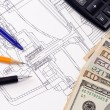 Dollars and pens on drafting of coupling — Stockfoto