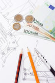 Pens and euro on drafting of construction machine — Stock Photo