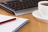 Tangentbord, anteckningsboken och kopp kaffe på bordet — Stockfoto