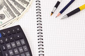 Pens, calculator and dollars — Stock Photo