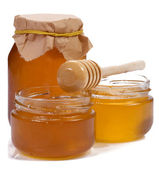 Glass jar full of honey and stick — Stock Photo