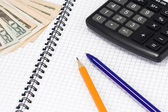 Calculator, pens and dollars at pad — Stock Photo