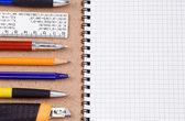 Canetas, lápis e almofada na textura de madeira — Fotografia Stock