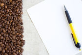 Pen at paper sheet with coffee — Stock Photo