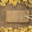 Raw pasta and price tag label on wood — Stock Photo