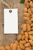 Nuts almond and tag price label on wood — Stock Photo