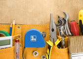 Tools in construction belt on wooden background — Stock Photo