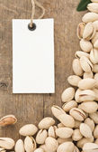 Pistachios nuts and tag price label on wood — Stock Photo