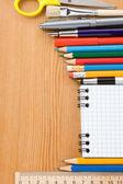 útiles escolares y comprobada aisladas en blanco — Foto de Stock