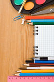 School supplies and checked notebook on wood — Stock Photo