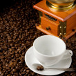 Empty cup and grinder on coffee beans — Stok fotoğraf