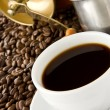 Cup of coffee and grinder on beans — Stockfoto