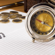 Compass, gold coin and pen on notebook — Stock Photo
