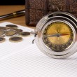 Compass, pen and coin on notebook — Stock Photo #11624429
