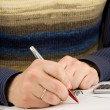 Male hand writing by pen on notebook — Stock Photo