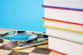 Książki, lupa i pióra na szachownicy — Zdjęcie stockowe