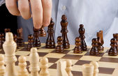 Male hand moving chess piece — Stock Photo