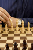 Man hand moving chess black piece — Stockfoto