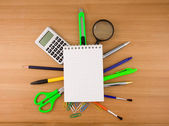 Office accessories under checked notebook on wood — Stock Photo