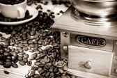 Coffee beans and wood grinder on sack — Stock Photo
