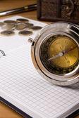 компас, перо и монета на ноутбуке — Стоковое фото
