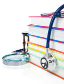 Pile of books, pen and stethoscope isolated on white — Stockfoto
