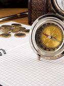 Kompas, gouden munten en pen op notebook — Stockfoto