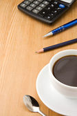 Pen, pencil and cup of coffee on wood — Stock Photo