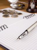 Pen and coin on notebook — Stock Photo