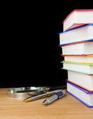 Hromadu knih a pera na černém pozadí — Stock fotografie