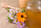 Honey in glass pot on sacking — Stock Photo