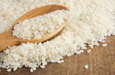 Rice grain in wooden spoon — Stock Photo