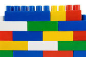 Assemble of colorful plastic bricks isolated on white — Stock Photo