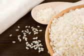 Rice grain and wooden plate — Stockfoto