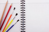 Brush and pencils on notebook — Stock Photo