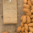 Nuts almond fruit and tag  label on wood - Stock Photo