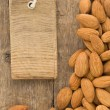 Stock Photo: Nuts almond fruit and tag label on wood