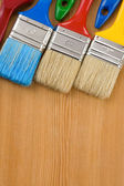 Colorful paintbrush on wood background — Stock Photo