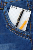Notebook and pencil on jeans packet — Stock Photo
