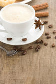 Cup of coffee with beans on wood background texture — Stock Photo