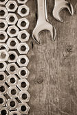Metal nuts and wrench tool on wood background — Stock Photo