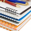 Pen and pencil at pile of notebook on white — Stock Photo