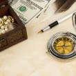 Pen, magnifier, feather and compass near dollars — Stockfoto